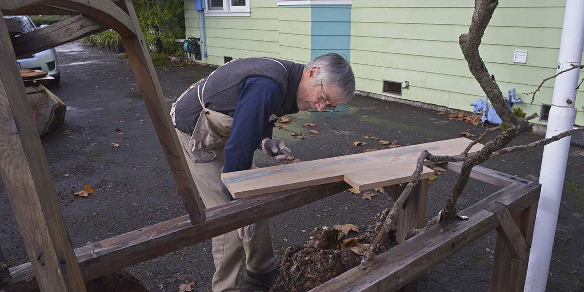 Bob working on wood in yard